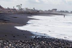 萨努尔,巴厘岛/印度尼西亚- 09 24 2015年:与黑火山的沙子的公开海滩 免版税图库摄影