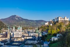 萨尔茨堡村庄谷和Hohensalzburg城堡在小山背景 免版税库存照片