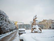 萨尔茨堡,奥地利- 2018年2月13日:在Mirabellplatz的罗马雕象冬天季节雪的 图库摄影