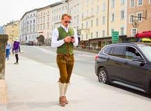 萨尔茨堡,奥地利- 2017年5月01日:穿传统奥地利服装的人努力去做与手机在晴朗的街道 免版税库存照片