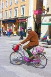 萨尔茨堡,奥地利- 2017年5月01日:穿有自行车的人传统奥地利服装在街道在晴天 免版税库存图片