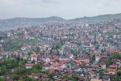 萨拉热窝、波黑在多云期间和rainly天的郊区的小山的鸟瞰图春天 清真寺罐头 库存图片