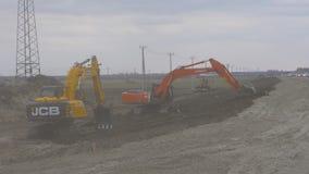 萨斯卡通,加拿大- 2018年5月15日 装载bould的专业履带牵引装置挖掘机在路附近 两台推土机看法  影视素材