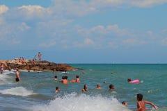 萨沃纳,意大利- 2017年7月02日:游泳在心神不安的海的人们 库存图片