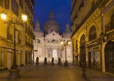 萨瓦格萨,西班牙- 2018年3月3日:大教堂Basilica del Pilar和Calle在黄昏的de阿方索 库存图片
