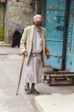 萨纳,也门- 12月23 :传统礼服的一个年长人步行沿着向下街道的 2014年12月23日在萨纳 库存照片