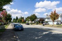 萨里,加拿大- 2018年9月19日:城市道路在与汽车的住宅区在一秋天好日子 免版税库存图片