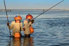 登巴萨,印度尼西亚-处于低潮中站立在浅水区的5月24日传统巴厘语渔夫在海滩在努沙Dua, Denpas 库存照片