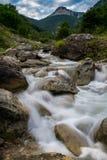 落下在小山下的山岩石河 库存照片