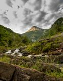 落下在小山下的山岩石河 免版税库存照片