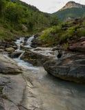 落下在小山下的山岩石河 图库摄影