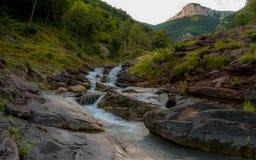 落下在小山下的山岩石河 库存图片