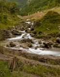 落下在小山下的山岩石河 免版税库存图片