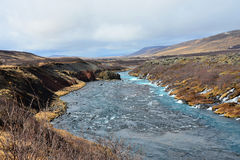 落与大海的Hraunfossar瀑布 免版税库存图片