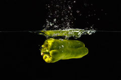 落入与飞溅的水的绿色bellpepper 库存照片