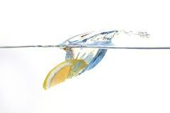 落入与飞溅的水的柠檬 免版税库存照片