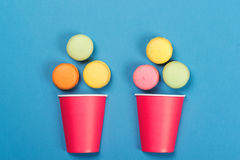 落入两红色纸杯的五颜六色的蛋白杏仁饼干 最小的conce 免版税库存图片