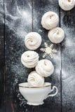 落入杯子的香草蛋白软糖和雪花 免版税库存图片