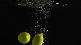落入水的柠檬射击了反对黑背景 股票视频