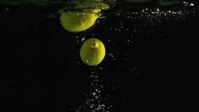 落入水的柠檬射击了反对黑背景 股票录像