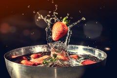 落入水的草莓与飞溅水在黑背景 老减速火箭的葡萄酒照片 库存照片