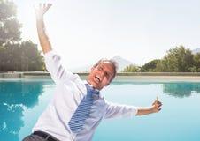 落入游泳池的商人获得乐趣 库存图片
