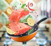 落入煎锅的飞行的鲑鱼排和香料 飞行 库存照片