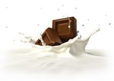 落入牛奶飞溅的两个巧克力块。 免版税图库摄影
