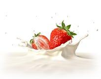 落入牛奶飞溅的两个草莓。 免版税库存照片