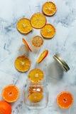 落入玻璃瓶子的干燥桔子和柠檬切片 免版税库存照片