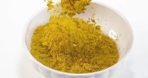 落入碗的咖喱粉反对白色背景,慢动作 影视素材