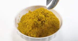 落入碗的咖喱粉反对白色背景,慢动作 股票视频