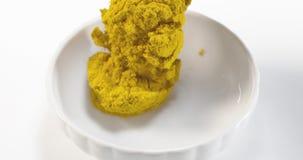 落入碗的咖喱粉反对白色背景, 股票录像