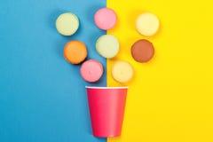 落入红色纸杯的五颜六色的蛋白杏仁饼干 最小的概念 免版税库存照片