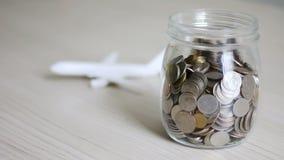 落入玻璃瓶子和迷离空中飞机的金钱硬币在挽救金钱后隐喻旅行和运输概念的 股票视频