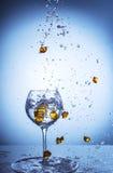 落入玻璃玻璃的下落和金黄小卵石,抽象 库存照片