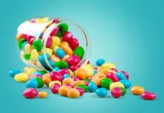 落在一个玻璃瓶子外面的五颜六色的糖果  免版税图库摄影