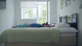 落在床藏品球拍的年轻疲乏的人在打网球以后在一舒适的酒店房间 E 股票录像
