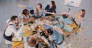 落在愉快的办公室商人的顶视图五彩纸屑庆祝团队工作成功与幼小母上司一起 影视素材