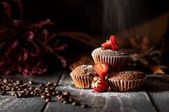 落在松饼的糖用在与咖啡豆的黄麻袋子放置的草莓 免版税库存照片