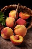 落在篮子外面的新鲜的桃子 免版税库存图片