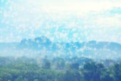 落在自然和山,抽象背景的模糊的照片的雪 免版税库存图片