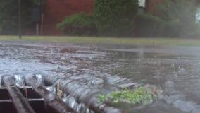 落在街道上和流经下水道流失的大雨 免版税库存图片