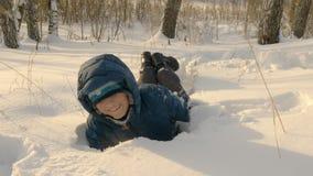 落在随风飘飞的雪的无忧无虑的少年男孩,当冬天步行在多雪的森林里时 股票视频