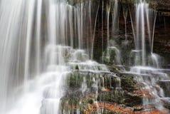 落在青苔和红色岩石的被弄脏的水细节  免版税库存图片