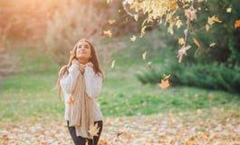 落在非常美丽的女孩森林画象的愉快的少妇的秋叶在秋天公园 免版税库存照片
