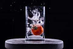 落在水中的蕃茄 免版税库存照片