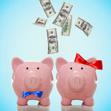 落或飞行在一对存钱罐夫妇外面的一百元钞票 免版税库存图片