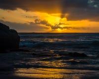 落日派出光芒从云彩的后面在Noordhoek海滩 免版税库存图片