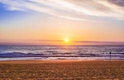 落日美妙地照亮镇静海洋和海滩 库存照片